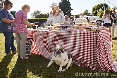 English Bulldog Sitting By Cake Stall At Busy Summer Garden Fete