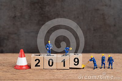 Year 2019 new year changing or just finished concept, miniature people workers building cube wooden block number 2019 with under