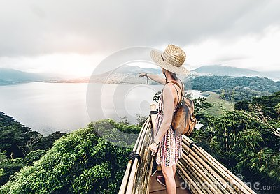 Happy woman pointing the horizon feeling free travelling the world on a inspirational background