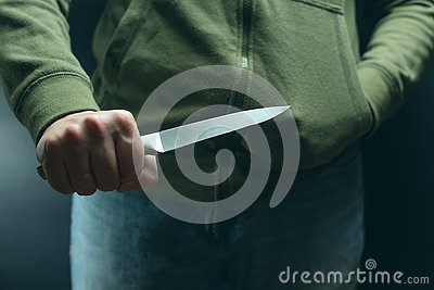 A criminal with a knife weapon threatens to kill. Criminality, crime, robbery thug