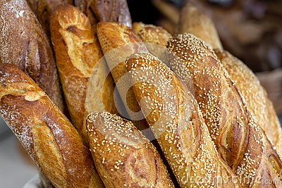 Traditional crusty French bread baguette in basket at bakery. Fresh organic pastry at local market. France cuisine background