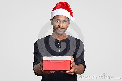 Isolated shot of serious black man wears Santa Claus headgear, carries little box of present, dressed in black jumper, poses over
