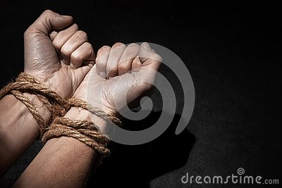 Man with hands tied with rope on black background. The concept of slavery or prisoner. Copy space for text.