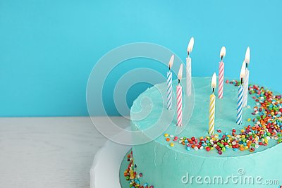 Fresh delicious birthday cake with candles on table against color background.