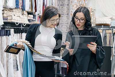 Two women working with interior fabrics digital tablet in showroom for curtains and upholstery fabrics, designer and buyer