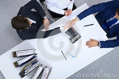 Business people shaking hands at meeting, view from above. Bookkeeper or financial inspector making report, calculatin