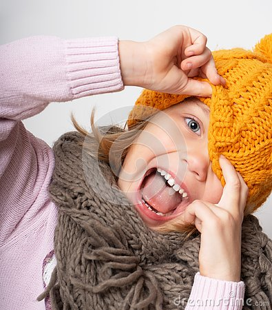 Close up face portrait of toothy smiling young woman wearing knitted hat and scarf.