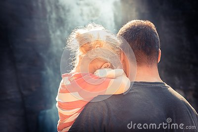 Father embracing daughter family lifestyle concept for togetherness and parenting rear view