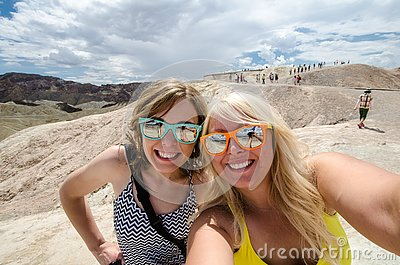 Two adult females take a selfie while at Zabriskie Point lookout in California Death Valley National Park