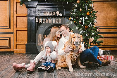 Theme Christmas and New Year family circle. Young Caucasian family with 1 year old child dog breed Labrador Golden Retriever