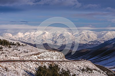 Rays of the winter sun dissipate fog in the Aragats mountains on the road to the city of Spitak
