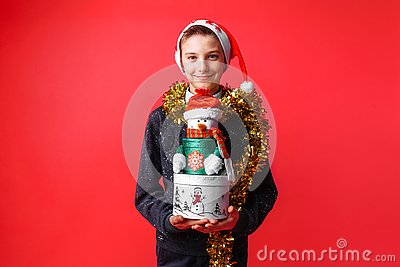 Teenage boy in Santa hat and tinsel on neck holding Christmas gift box on red background