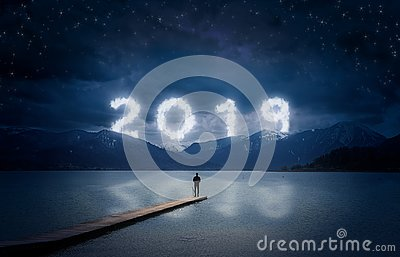 New year background, young man standing on a jetty in a lake and looking to the mountains under the dark sky with cloudy text 2019
