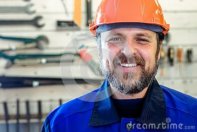 A man with a beard in a helmet and work clothes is smiling a snow-white smile against the background of a stand with tools.