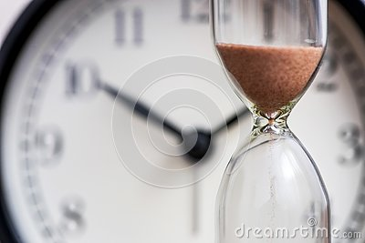 Hourglass on the background of office watch as time passing concept for business deadline, urgency and running out of time. Sand