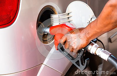 Detail hand of worker man refuelling car at the petrol station. Concept photo for use of fossil fuels gasoline, diesel engine