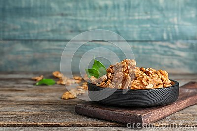 Plate with tasty walnuts on wooden table.