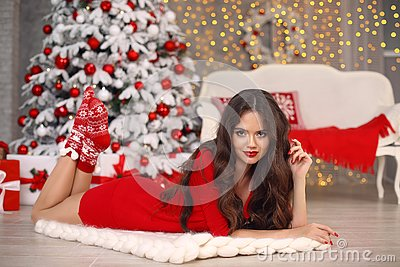Christmas. Beautiful santa girl. Smiling woman with long hair and red lips makeup lying on white knitted chunky yarn blanket in