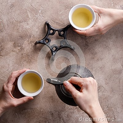 Still life with traditional Asian herbal tea in an old cast-iron teapot with pyalas in hands on a textured background. Square