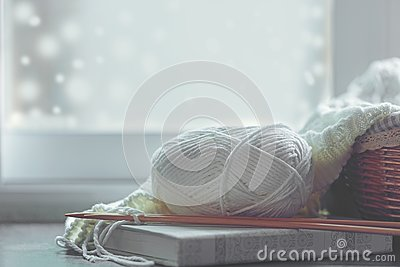 stock image of cozy winter home with warm knitted sweaters and ball of yarn near windowsill, home hobbies, vintage tone.