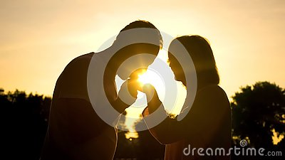 Silhouette of gentleman kissing wife's hand, senior couple in love, romance