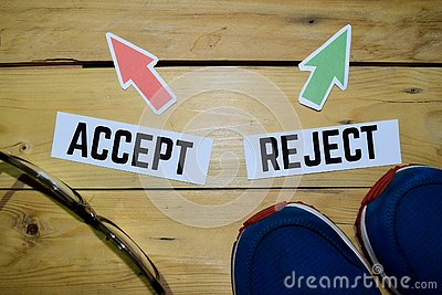 Accept or Reject opposite direction signs with boots, eyeglasse and sneakers on wooden