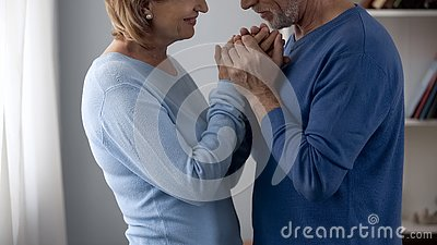 Retiree couple holding hands, looking at each other with love and gratefulness