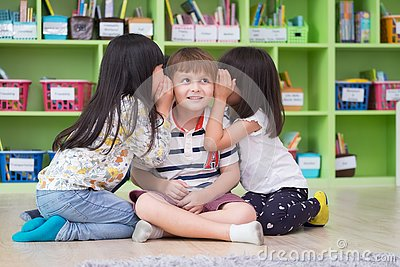 Two girl kids whisper secret at ear of boy in library at kindergarten preschool,Fun and happy children,back to school concept