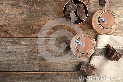 Flat lay composition with jars of tasty chocolate milk and space for text on wooden background.