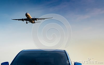 stock image of commercial airline. passenger plane landing approach blue suv car at airport with blue sky and clouds at sunset. arrival flight.