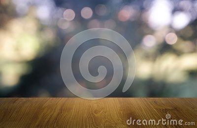 Empty wooden table in front of abstract blurred green of garden and house background. For montage product display or design key