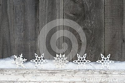 Rustic winter background with glitter snowflakes and snow on wooden texture. Christmas and New Year greeting card background