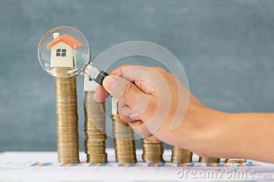 Close-up Of A Businessperson`s Hand Looking At House Model Through Magnifying Glass, House searching concept with a magnifying