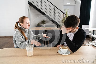 Bad relationship concept. Man and woman in disagreement. Young couple sitting in cafe having quarrel, offended wife and