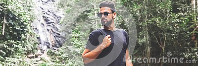 Handsome young stylish man in black t-shirt and sunglasses is engaged in trekking in the green jungle