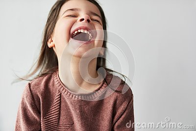 Studio closeup horizontal portrait of happy beautiful little girl smiling joyful and wearing sweater isolated on a white studio