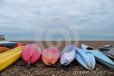 Colourful canoes on pebbly beach at Hove, East Sussex, UK. Photographed on a cold, calm winter`s day.