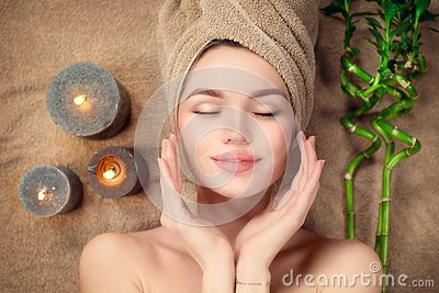 Beautiful spa woman with a towel on her head lying and touching face skin. Skincare