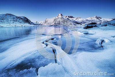 Mountain ridge and ice on the frozen lake surface. Natural landscape on the Lofoten islands, Norway.