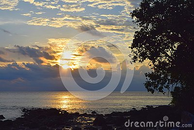 Rising Sun with Golden Sunshine with Clouds in Sky with Lining over Sea and Contours of Tree and Stones - Neil Island, Andaman