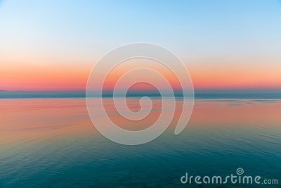 Beautiful multicolor sunset reflected in the waters of Lake Garda, Italy. Skyline. Visible coastline in the evening fog. Winter