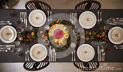 Christmas table setting with baubles arranged on plates and green and red table decorations, overhead view