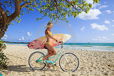 Girl on her bicycle with surfboard