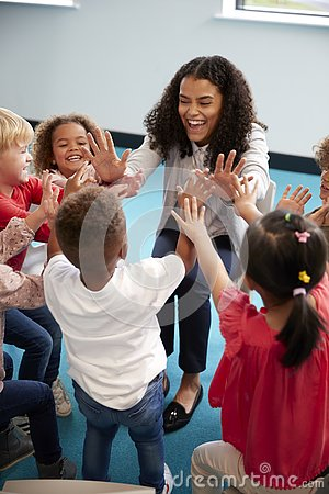 Elevated view of infant school children in a circle in the classroom giving high fives to their smiling female teacher, vertical,