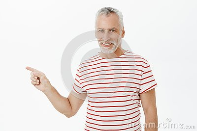 Waist-up shot of delighted carefree charismatic happy old man with grey beard in striped t-shirt smiling satisfied and