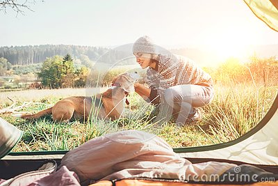 Woman and her dog tender scene near the camping tent. Active leisure, traveling with pet6 simple things concept image