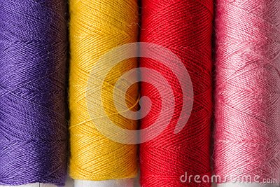 stock image of row of multicolored rainbow palette sewing threads on cardboard spools. crafts hobbies local artisan business interior decoration