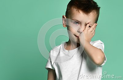 stock image of portrait of unhappy sad bored kid boy leaning head on palm looking with upset