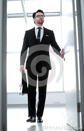 Businessman with a leather briefcase entering his client`s office.