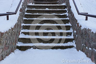 Old gray concrete staircase with stone steps under white snow
